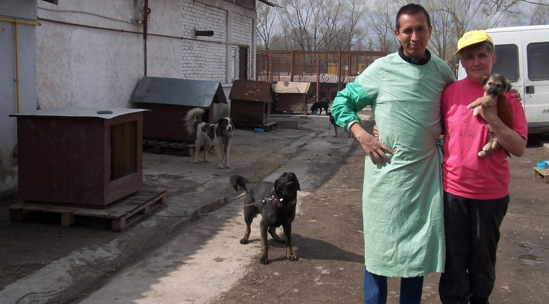 Volunteer and staff member stand outside the Veterinary Medicine placement in Romania.